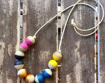 half painted pink, yellow, blue, black and gold hand painted wooden bead necklace