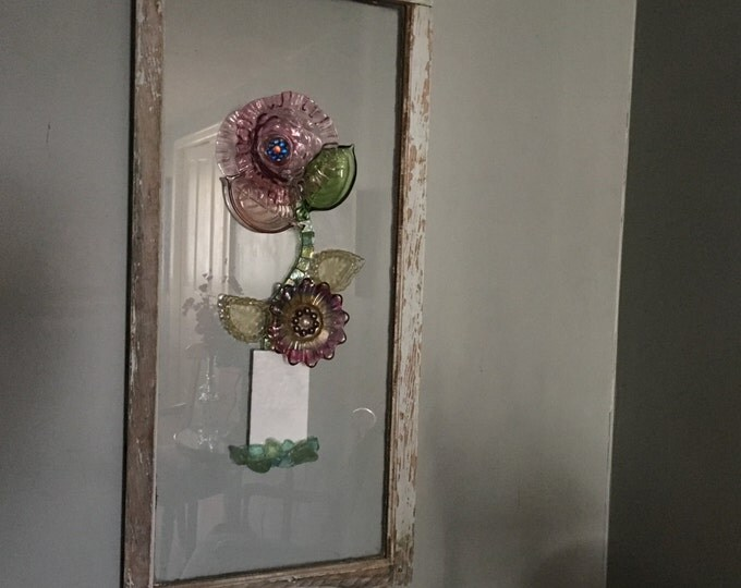 old refurbished window designed with various pieces of glassware to make a unique floral display