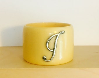 An early 20th century bakelite and silvrr napkin rings with ornate letter J