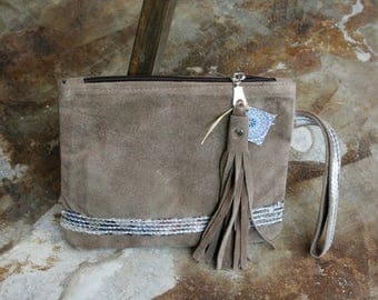 A beautiful leather suede brown clutch with silver sequin decorating line comes with a suede tassel and a beautiful wrist-let