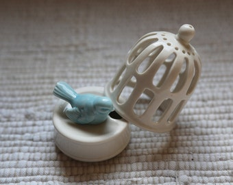 Porcelain cage with small bird. Decor. Accessory