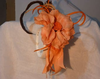 Orange headdress with feather straps gross and central flower.
