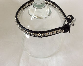 Bracelet in black leather with silver beads a crystal style button fastening. Approx length 20 cm, width 8mm