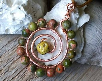 Handmade spiral copper pendant surrounded by stones.