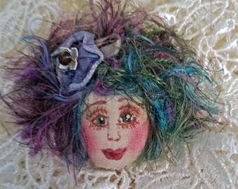 Whimsical, fiber sculpted art doll face pin, with silk face