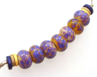 Handmade Lampwork Glass Beads - 7 bead set. Color splashes of purple on shades of opal yellow and pale peach.