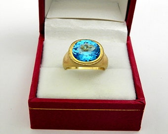 AAAA Neon Blue London Blue Topaz Top Color   11x9mm  3.00 Carats   in Ladies 18K Yellow gold cocktail ring 10 grams. 2623