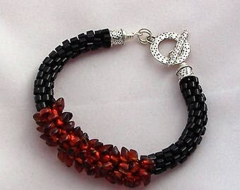Black Beaded Kumihimo Woven Bracelet with a Focal of Flame Colored Magatama Beads by Carol Wilson of Je t'adorn