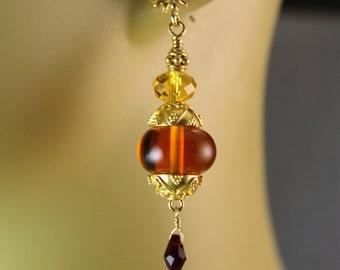 The Laelia Deep OrangeLampwork Glass, Swarovski Sunflower Rondelles Bali Vermeil Earrings hung on Bali Vermeil Sunflower Posts