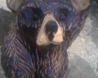 chainsaw carved sitting bear waving