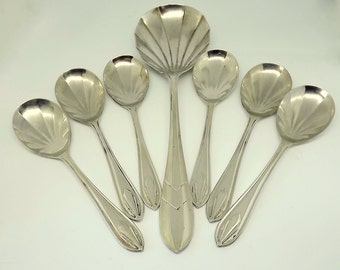 Six shell shaped and silver plated dessert spoons, fruit spoons with their serving spoon