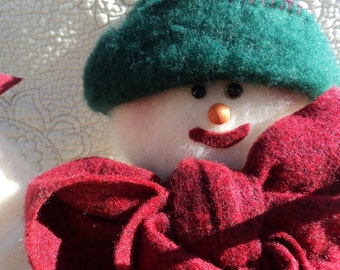 Handmade plush snowman with accents of felt in green, red, yellow