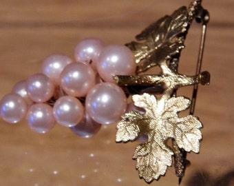 A vintage bunch of grapes brooch in imitation pearl and gold tone metal