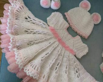 Pink and white crochet baby outfit with roses and lace ruffles.