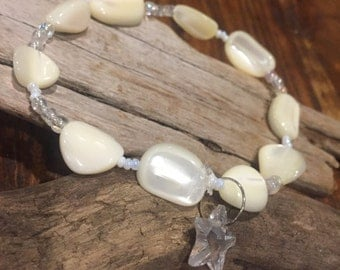 Beautiful beachy anklet with a shimmering iridescent starfish charm.  Ivory colored shell beads and seed beads.