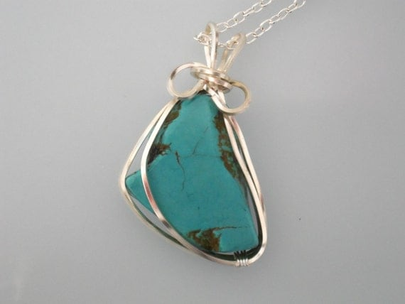 Wire wrapped pendant. Turquoise wrapped with silver plated wire. Silver chain.
