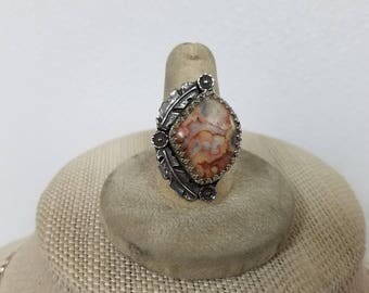 Sterling silver ring size 8 1/4 . It has an 16 x 21 mm fan shaped crazy lace agate with a pair of feathers and 3 small blossom. new band