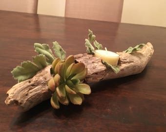 Driftwood candleholder with succulents and greenery.