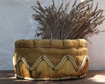 Rustic basket made by hand from corn leaves and grey canvas