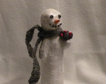 Snowman with grey scarf and pinecones