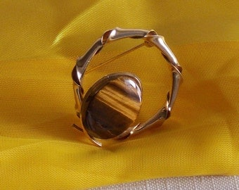 A Special reduced price... gold metal brooch with a tiger's eye stone.