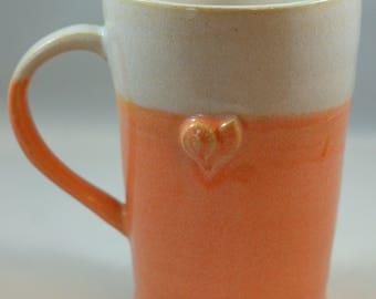 Wheel thrown orange and white mug with starfish and nautilus shell