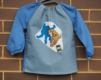 Kids art smock apron. Toddler size long sleeve waterproof art smock fits age 2-3 years. Blue with monsters motif.