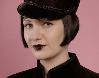 Military cap of black feathers and gloss pvc peak
