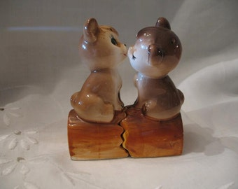 Salt & pepper shakers young lion and lioness is cooing on a log. Salt and pepper.