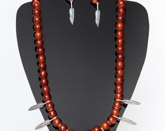 Beautiful maroon beaded necklace with feather pendants.