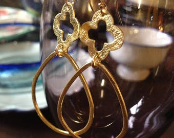Brushed gold quartefoil earrings with large brushed gold loops.