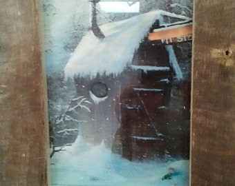 Old outhouse picture in weathered barn board frame