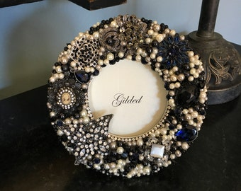 "Sadie is a round 7"" frame with a 4x4 opening embellished with vintage jewelry, crystal and pearls."