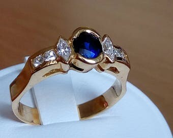 Gold ring with central blue sapphire and navette and brilliant cut side diamonds