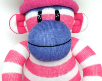 Pretty small pink and white candy stripe Sock Monkey with purple face and dotty pom pom hat