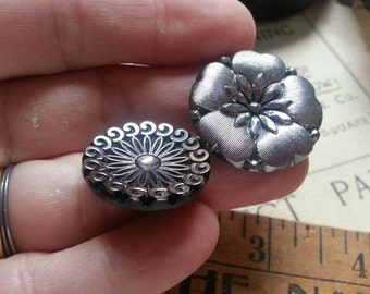 "Five, Silver Luster, Glass Buttons. Black Glass Buttons. Measure 7/8"" and 1 1/16""."