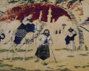 Religious tapestry wall having in bright, vivid colors, with camel, palm trees, peasants, temples and Mary and Joseph