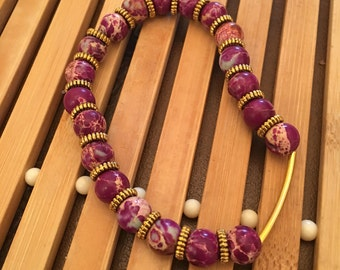 7.5 inch gold and purple beaded stretch bracelet.