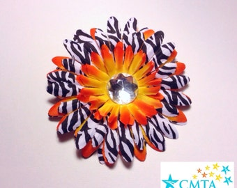 One orange and zebra hair flower with rhinestone. Portion of sale goes to charity.