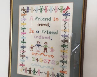 A vintage hand embroidrted cross stitch framed picture.