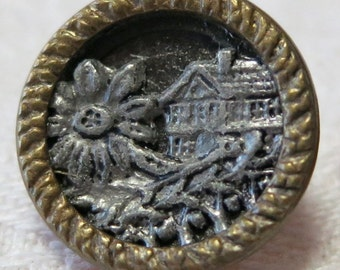 """Vintage metal button, 0.5""""ins across, brass toned rim, silver toned house with flower  in foreground on black field.Loop. PFM13.4-16.8-19."""
