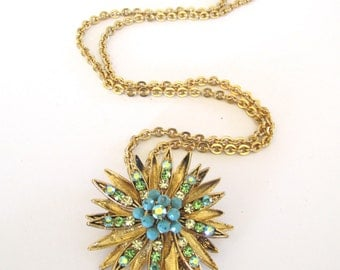 Gold tone metal Starburst brooch and pendant with green rhinestones and blue beads