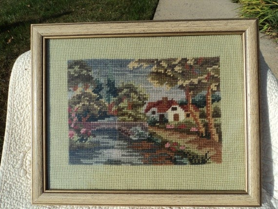 Lovely vintage hand made needlepoint of rustic home and bridge over stream/framed and under glass