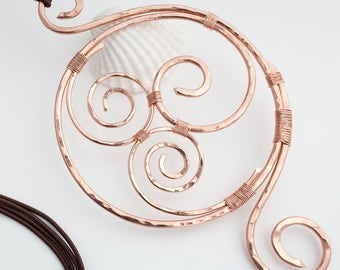 A large round copper pendant necklace, a wire wrapped handmade jewel, with shapes of spirals, a unique piece of copper jewelry