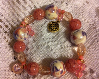 Pink shades mixed stretch bracelet with Celtic knot charm.