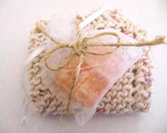 Knitted washcloth with sample of handmade soap, lightly scented, neutral beigh color with flecks of pastel blue, pink