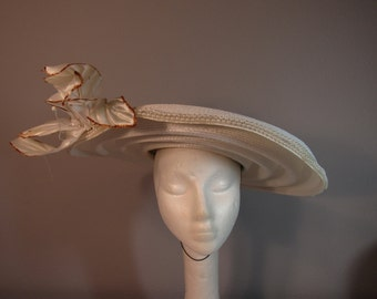 An Original Hat by Dolores M. Chestnut, cartwheel style hat with flower and beads.