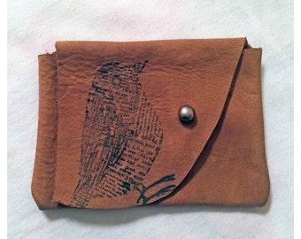 Leather pouch with newsprint bird print
