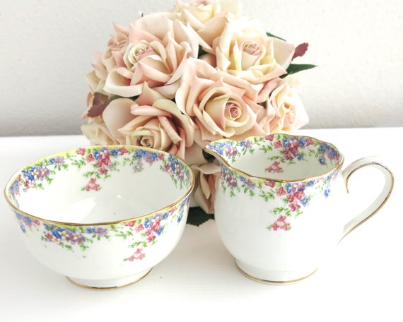 Sugar bowl and creamer, Crown China, Maytime pattern, edges trimmed with cascading pink and blue flowers, England, very pretty, 1930s