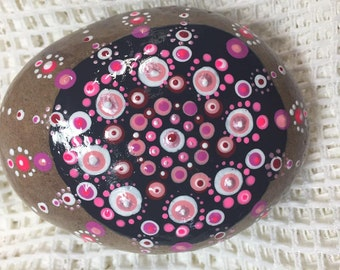 Round River rock painted with black background with Pink mandala to be used as garden stone or paperweight.